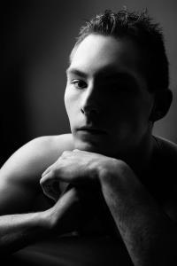 Junger-Mann-schaut-ernst-halb-dunkel-Fotostudio-blendenspiel