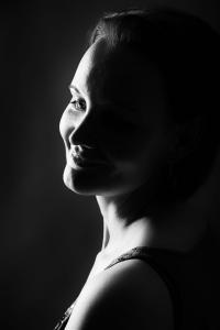 Junge-Frau-lächelt-Gesicht-im-dunkeln-Fotostudio-blendenspiel